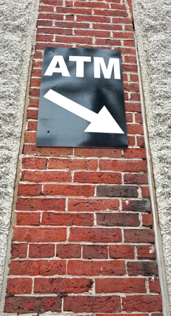 ATM sign attached to brick wall with arrow pointing down. Vertical. Reklamní fotografie