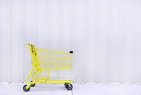Yellow shopping cart on sidewalk against grey  gray wall. Horizontal. Banco de Imagens