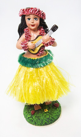 Happy hula girl dashboard souvenir wearing grass skirt, flower leis, and holding ukulele. White background. Vertical. Stock Photo