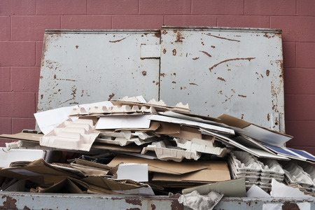 discarded: Close up of dumpster filled with cardboard for recycling. Lid open against reddish wall. Horizontal.