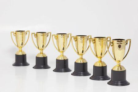 Gouden trofeeën in een lichte diagonaal op witte achtergrond. Horizontaal.
