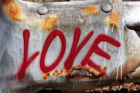 LOVE spray painted on dented, rusty Pittsburgh highway guardrail.