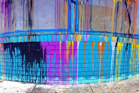 Colorful sloppy paint spill on side of building. Vertical. Stock Photo