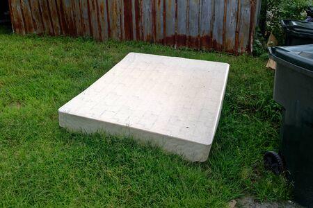 Abandoned white mattress on grass. Horizontal.