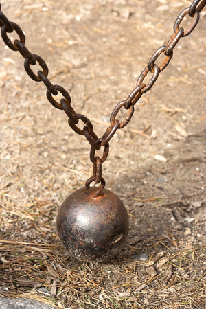 Old counterweight ball and chain still in use on gate.