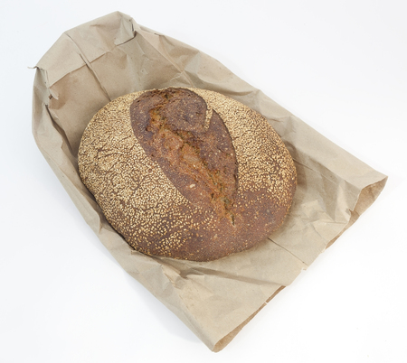 Isolated freshly baked sesame rye resting on brown paper bag.