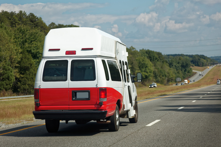 Rear and side view of ambulance emergency vehicle on highway. Horizontal. Stock Photo