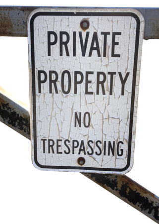 Isolated PRIVATE PROPERTY NO TRESPASSING sign mounted on partial metal gate. Stock Photo