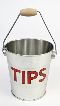 gratuity: TIPS concept with shiny silver bucket. Isolated. Stock Photo