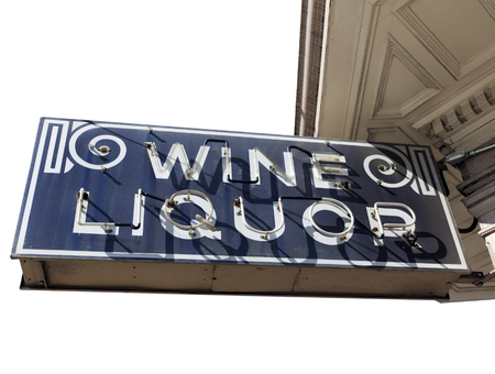 b w: Vintage black and white WINE AND LIQUOR sign attached to building. Isolated. Stock Photo