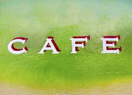 CAFE sign on green wall.