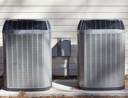 Two side-by-side heats pumps on concrete slab against house wall.