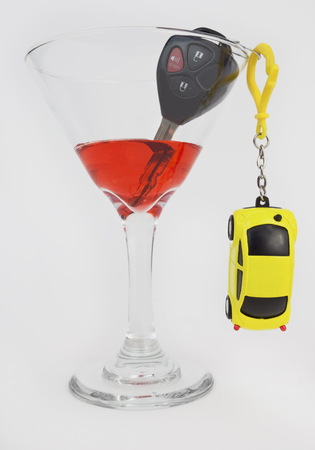 to warn: Drinking and driving concept with martini, model car, and keys.
