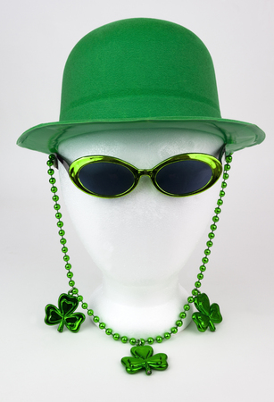 St. Patricks Day green topper, clovers, beads, and sunglasses on a white styrofoam mannequin head. Isolated.