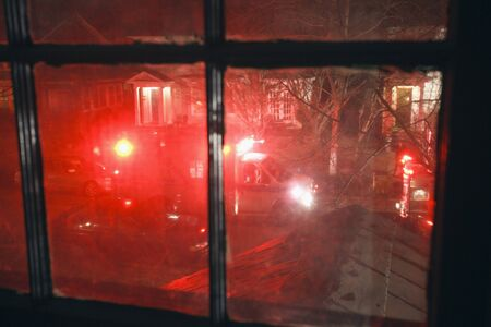 responding: Nighttime red emergency lights flashing in residential neighborhood as seen from upstairs window.
