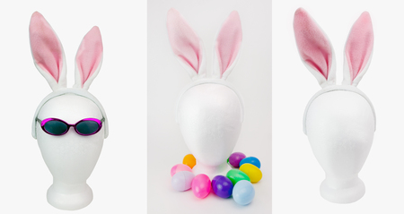 Styrofoam mannequin heads with Easter decorations: sunglasses, colorful plastic eggs, and furry pink bunny ears. Isolated.