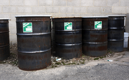 dumps: Non bio-hazardous oil drums stacked against cinder block wall. Stock Photo