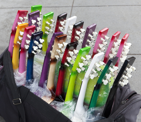 Street vendors colorful in expensive guitars with focus on necks. Stock Photo