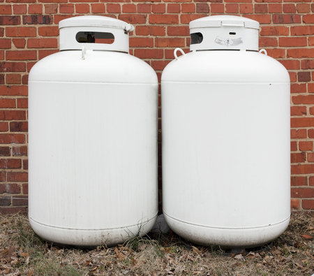Two propane white canisters against brick wall. Stock Photo