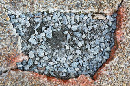 Gravel maintenance on damaged pebble sidewalk.