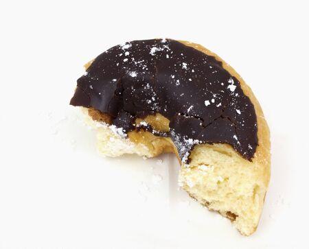 Leftover, partially eaten piece of chocolate covered doughnut.