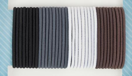 Zwarte, grijze, grijze, witte en bruine elastische haarbanden gemonteerd op blauwe presentatiekaart.