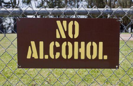 Geel op bruin GEEN ALCOHOL-bord bevestigd aan openbare parkomheining.