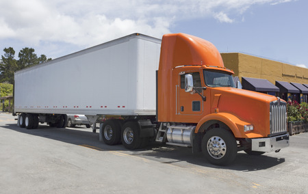 Side view of parked semi truck with orange cab.