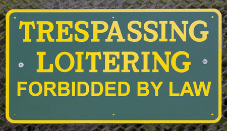 Misspelled TRESPASSING LOITERING sign. Yellow lettering on green background.