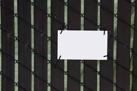 Blank white sign attached to backlit wooden fence. Copy space. Reklamní fotografie