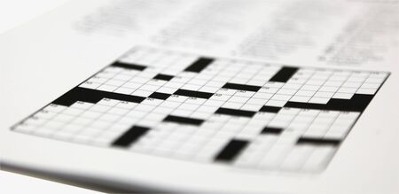 Shallow focus on daily newspaper crossword puzzle. Stock Photo