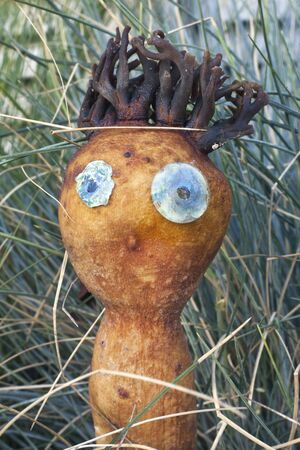 Odd, silly, bizarre doll-like figure in grass made from dried Pacific seaweed.
