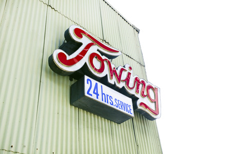 TOWING sign attached to side of industrial building.
