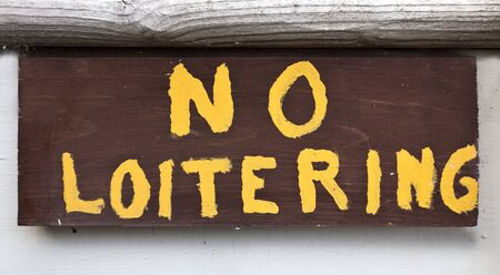 Sloppy handmade yellow on brown NO LOITERING sign. Stock Photo