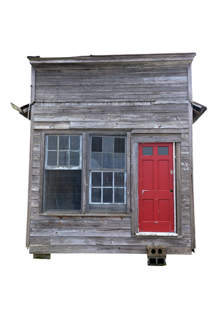 front view: Front view of abandoned, deserted wood building with red door. Isolated.