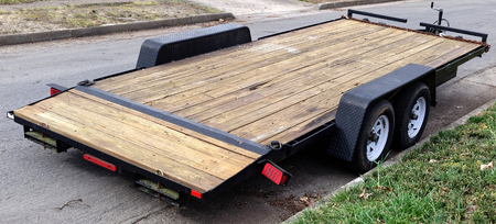 Empty flatbed wood trailer parked on residential street. Stock fotó