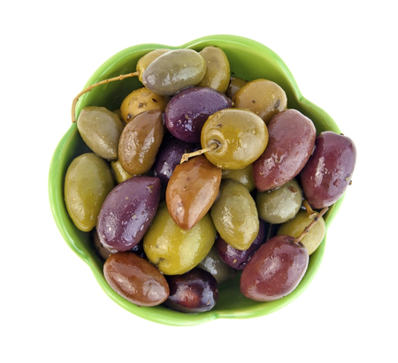 Looking down on a green bowl filled with mixed Greek olives. Isolated.