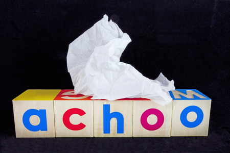 Cold and flu season concept with tissue and toy blocks.