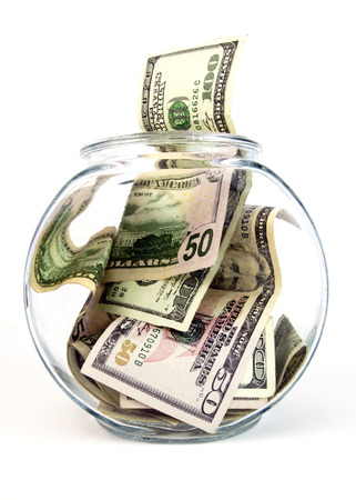 Clear glass jar filled withUnited States currency. Isolated.