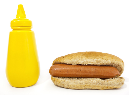 Hot dog in whole wheat bun with squeeze bottle of yellow mustard. Isolated. Horizontal Banco de Imagens