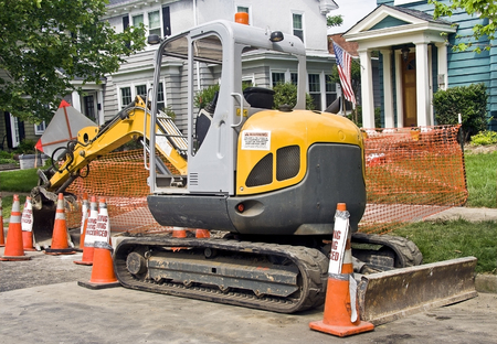 Heavy construction machinery parked on residential neighborhood street.