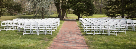 Rows of white event chairs in park setting with lawn foreground and tree background. Banco de Imagens