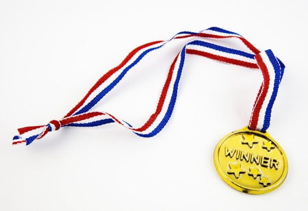 Plastic gold colored WINNER medal with red, white, and blue ribbon. White background. Stok Fotoğraf