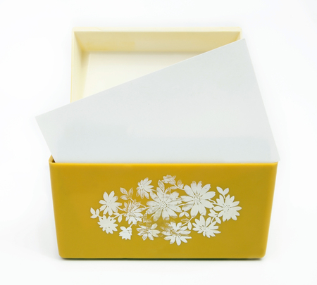 Front view of vintage 1970s yellow recipe box with blank card. Isolated.