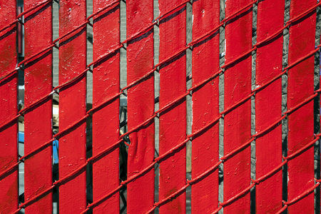 Detail close up of bright red wood slats and chain link fence.
