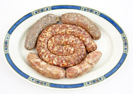 Plate filled with assorted types of raw sausages. Isolated. Banco de Imagens