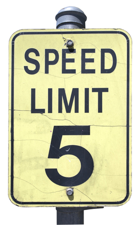 Weathered and yellowed black and faded yellow SPEED LIMIT 5 sign. Isolated. Vertical. Banco de Imagens