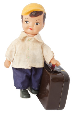 Vintage metal wind up toy. Boy with a suitcase. Isolated.