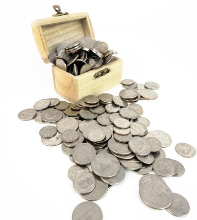 Wood chest filled with silver clad US coins. Isolated. Vertical. Banco de Imagens