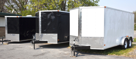 Three black and white transport trailers for sale or rent in a row. Stok Fotoğraf